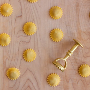 Homemade anolini pasta with brass ravioli stamp made in Italy